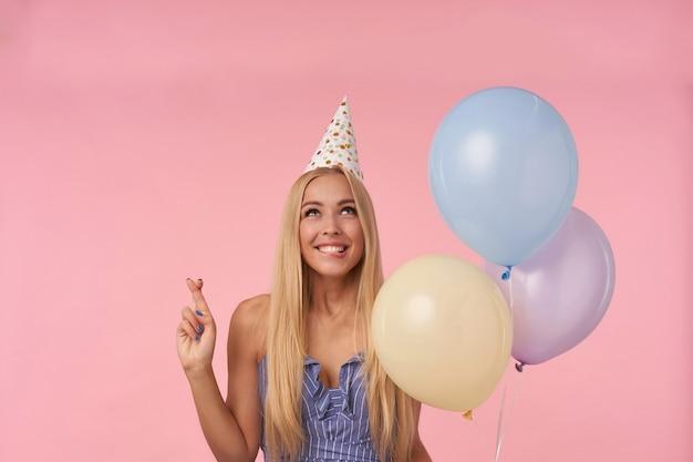 Felice attraente giovane femmina bionda che esprime desiderio e dita incrociate per buona fortuna, tenendo un mazzo di palloncini di elio mentre posa su sfondo rosa in abito estivo blu e cappello di compleanno