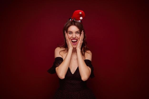 빨간 점과 산타 모자 포즈와 우아한 드레스를 입고 행복 매력적인 젊은 갈색 머리 아가씨, 흥분된 얼굴로 광범위하게 미소