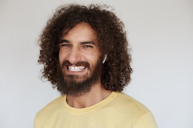 幸せな魅力的な若いブルネットの巻き毛の男は、彼の楽しい感情を示し、広く笑顔で彼の白い完璧な歯を示しています