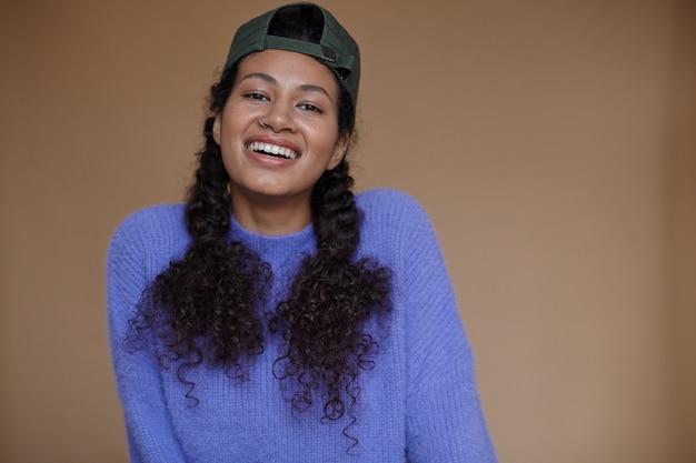 カジュアルな服と野球帽を身に着けている編みこみの髪型で、ポーズをとっている間元気に笑って、幸せな魅力的な若いブルネットの暗い肌の女性