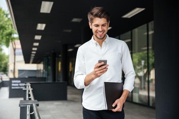 Счастливый привлекательный молодой бизнесмен прогулки и использование мобильного телефона на открытом воздухе