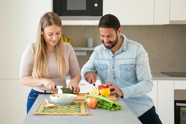 幸せな魅力的な若いカップルが一緒に夕食を作って、台所のまな板で新鮮な野菜をカット、笑顔で話しています。家族の料理のコンセプト