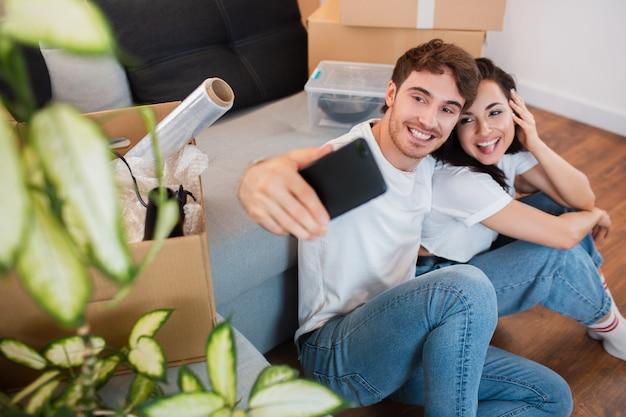 Счастливая привлекательная молодая пара двигается, делает селфи, обнимается и улыбается, сидя среди картонных коробок