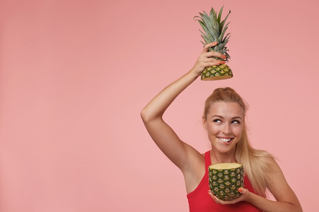 Happy attractive young female with long blonde hair posing, looking upwards and smiling, biting underlip and having fun with cut pineapple