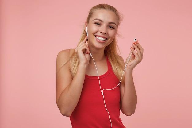 Счастливая привлекательная молодая женщина с длинными светлыми волосами, торчащими из наушников во время прослушивания музыки, в повседневной одежде, изолированные