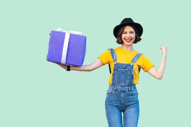 힙스터를 입은 행복한 매력적인 어린 소녀는 데님 작업복을 입고 검은 모자를 쓰고 이빨 미소로 크고 무거운 선물 상자를 들고 카메라를 바라보며 강한 팔을 보여줍니다. 스튜디오 촬영, 녹색 배경