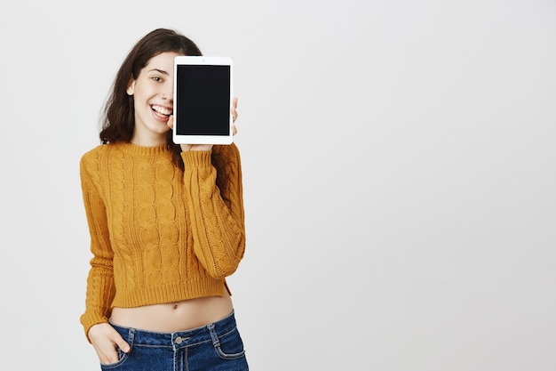 Felice ragazza attraente che mostra lo schermo della tavoletta digitale