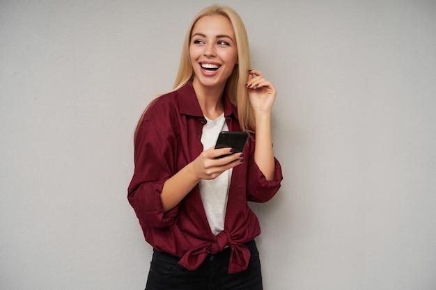 幸せな魅力的な若い長い髪のブロンドの女性は魅力的な笑顔で脇を見て、彼女の完璧な白い歯を示し、明るい灰色の背景の上にポーズをとっている間彼女の楽しい感情を示しています