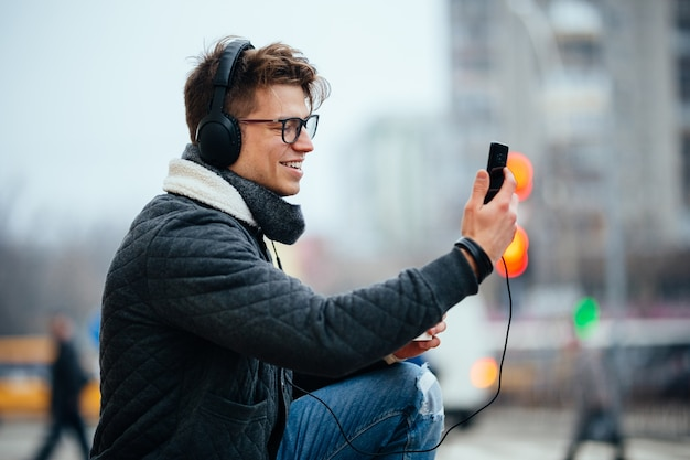 Happy attractive young man in headset taking selfie on his mobile phone