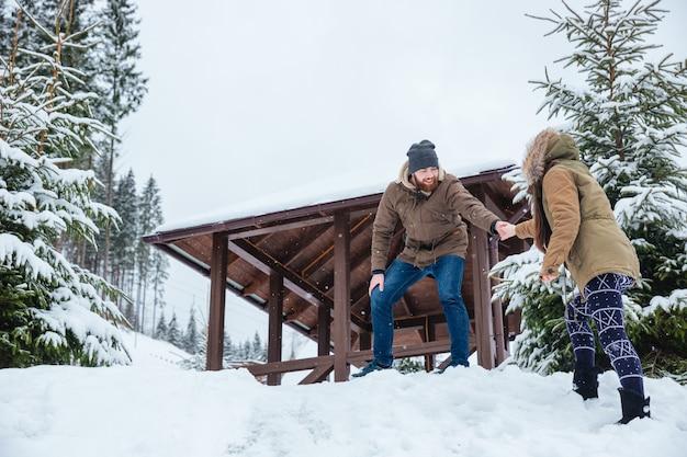 겨울에 산에서 산책에 그의 여자 친구를 돕는 행복 매력적인 젊은 남자