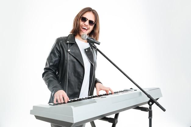 長い髪のサングラスでマイクで歌い、白い背景の上のシンセサイザーで遊んで幸せな魅力的な若い男