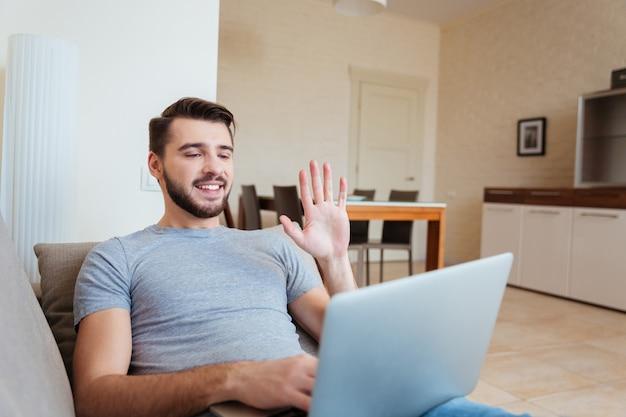 소파에 누워 노트북을 사용하여 화상 회의를 갖는 행복 매력적인 젊은 남자