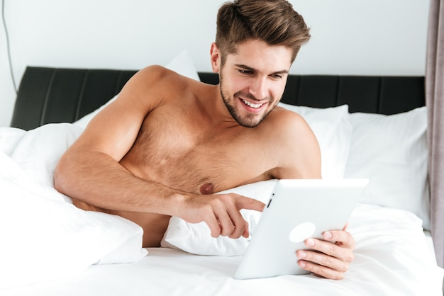 Счастливый привлекательный молодой человек с помощью планшета в постели утром