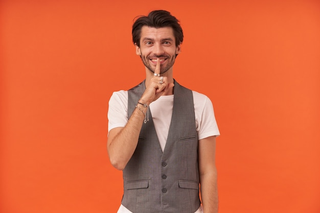 Happy attractive young man with bristle smiling and showing silence sign isolated