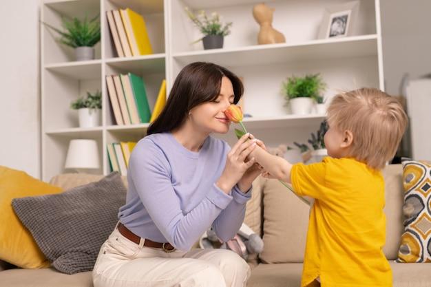 행복 한 매력적인 젊은 어머니가 소파에 앉아 집에서 아들에 의해 주어진 꽃 냄새