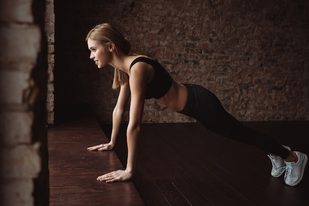 Happy attractive young sportswoman doing pushups