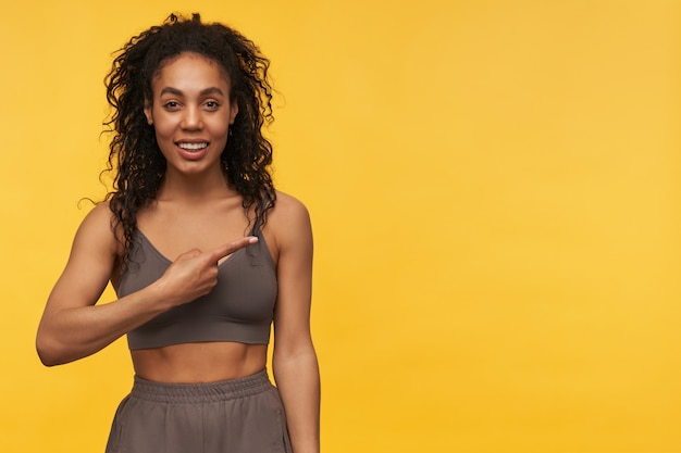 Happy attractive young sportswoman standing and pointing away to the side at empty space isolated over yellow wall looking at front