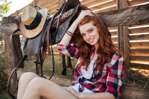 농장에 앉아 행복 한 매력적인 젊은 여자 카우걸