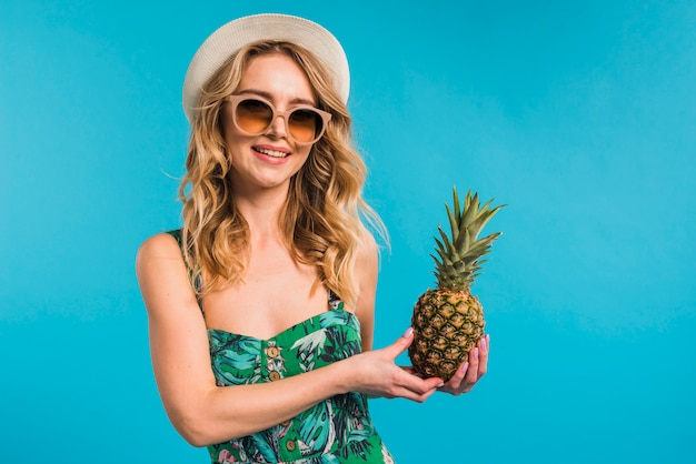 Happy attractive young woman in dress with hat and sunglasses holding fresh pineapple