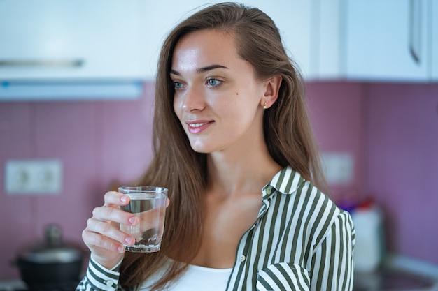 自宅のキッチンで透明な精製水のガラスを保持している幸せの魅力的な若い女性