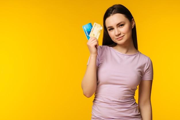 Счастливая привлекательная молодая женщина, держащая и показывающая две кредитные карты над желтым