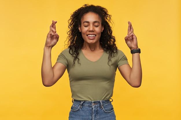 カジュアルな服を着た幸せな魅力的な若い女性は、目を閉じたまま、指を黄色の壁の上で孤立させた