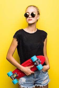Счастливая привлекательная молодая женщина в солнцезащитных очках, сидя на скейтборде на желтом фоне