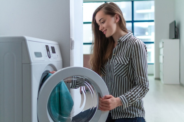 Счастливая привлекательная прачечная загрузки молодой женщины в стиральной машине дома