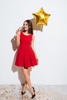 Happy attractive young woman in red dress holding star shaped balloon and drinking champagne over white background