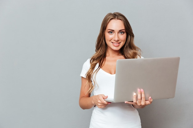 Happy attractive young woman standing and holding laptop over gray wall