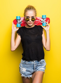 Happy attractive young woman in sunglasses sitting on skateboard over yellow background