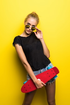 Felice attraente giovane donna in occhiali da sole seduto su skateboard su sfondo giallo