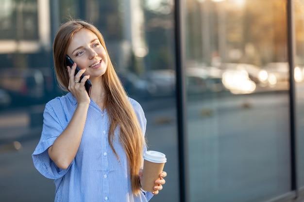 Счастливый привлекательная молодая женщина, говорить на смартфоне, держа забрать чашку кофе