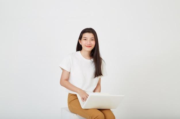 노트북 컴퓨터를 들고 다리를 꼬고 앉아 흰색 스튜디오 배경의 빈 공간을 바라보는 행복한 매력적인 젊은 여성
