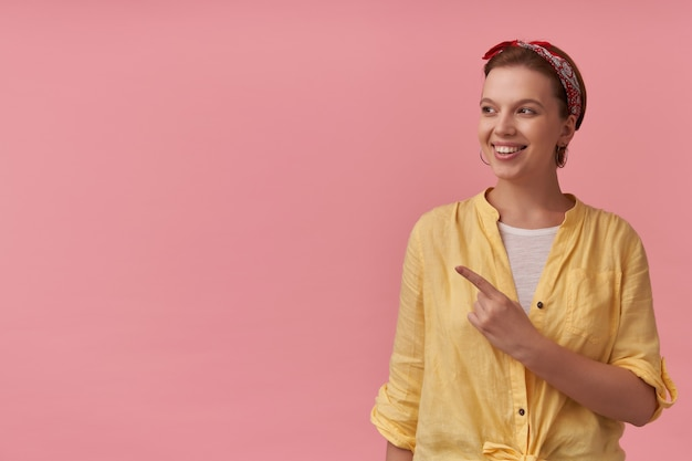 Happy attractive young woman in yellow shirt with headband on head looking and pointing away to the side at copyspace over pink wall