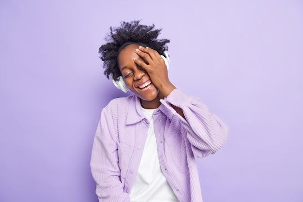 행복한 정통 감정 개념입니다. 곱슬 머리를 가진 평온한 즐거운 어두운 피부의 여성은 얼굴을 손바닥으로 활짝 웃게 만듭니다.