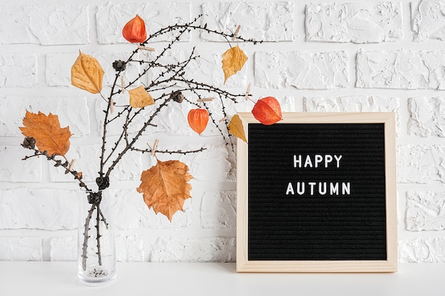 Happy autumn text on black letter board and creative bouquet of branches