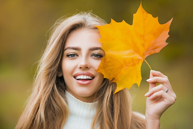 Happy autumn woman having fun with leaves outdoor in park. close up portrait photo of young girl on blurred park fall background, leaves falling.