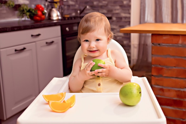Happy baby 10-12 months eats fruit: orange, apple. portrait of a happy girl in a highchair in the kitchen