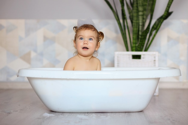 Happy baby bathes in the bathroom