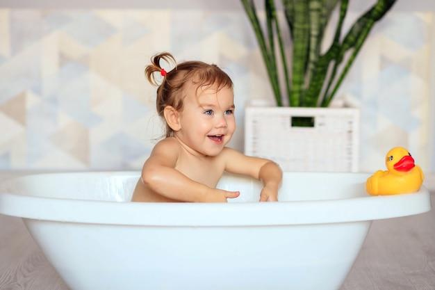 幸せな赤ちゃんはバスルームで入浴します