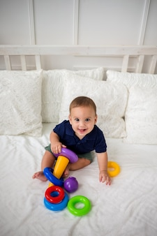 Счастливый мальчик и играет с игрушкой-пирамидкой. вид сверху