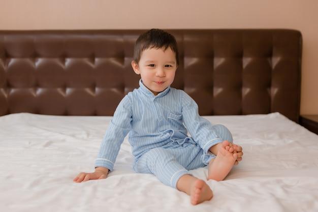 青いパジャマ姿で幸せな男の子は家のベッドの上にあり、上からの眺め、テキスト用のスペース