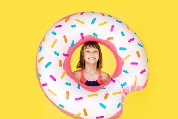 Счастливый малыш мальчик в купальнике с кольцом плавательный пончик на желтой цветной стене