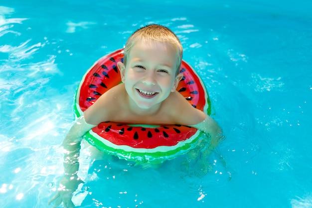 幸せな男の子は真っ赤なインフレータブルサークルと青いプールで泳ぐことを学ぶ