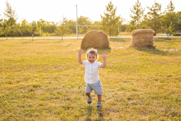 Happy baby boy on natural background in summer