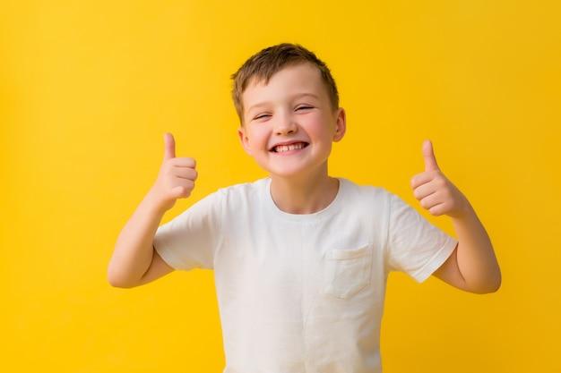 黄色の背景に白いtシャツで7歳の幸せな男の子