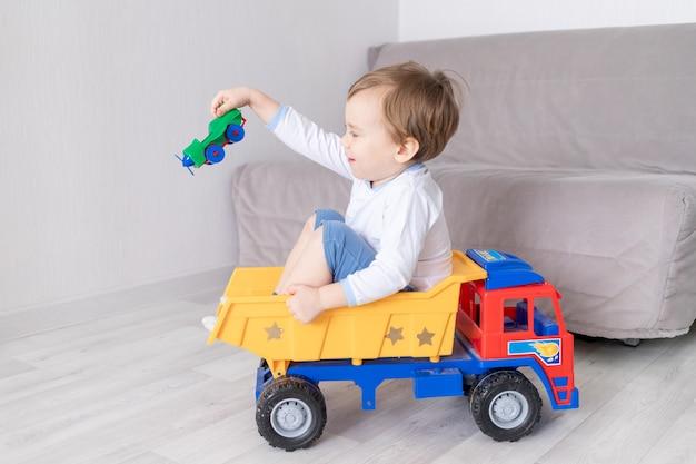 행복 한 아기 소년 집에서 놀고, 타자기를 타고, 아이의 게임의 개념