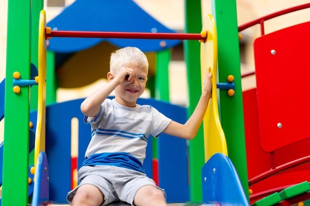 夏の庭の遊び場で遊んで幸せな男の子