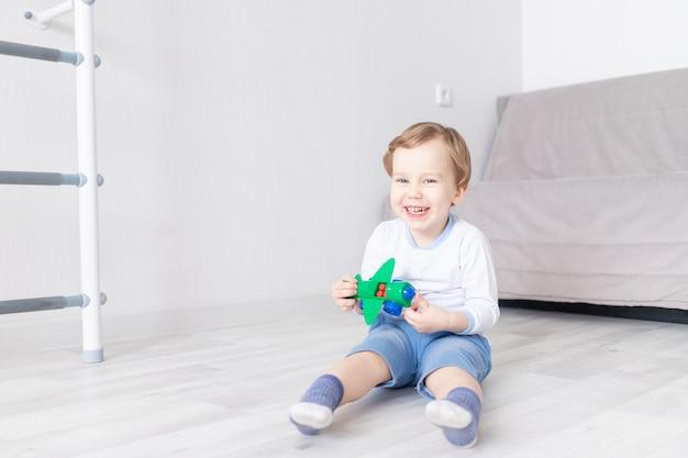 행복 한 아기 소년 집에서 비행기와 웃음을 재생 프리미엄 사진